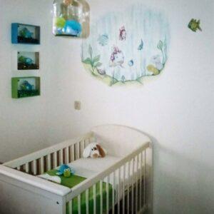 Muurschildering voor in de babykamer met goudvisjes boven de commode