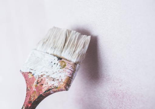 Kwast met witte verf op een witte muur voorbereidingen muurschildering